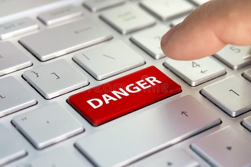 Palavra do perigo no botão do teclado de computador O dedo pressiona o botão da cor no teclado cinzento imagem de stock