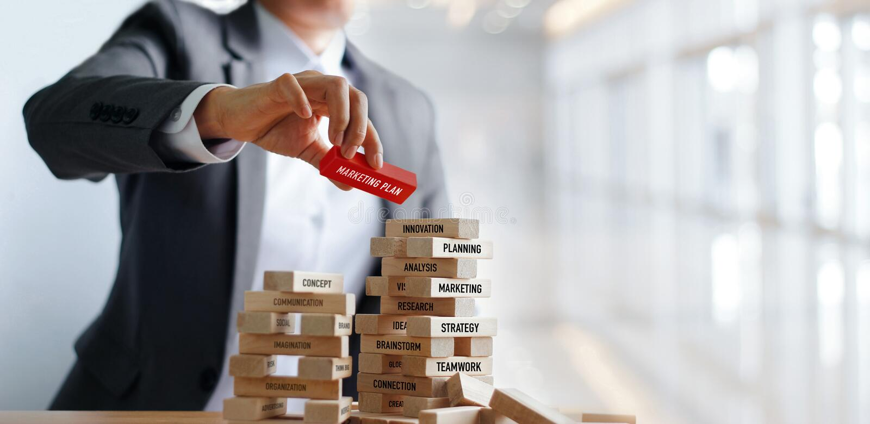 Palavra do plano de marketing da terra arrendada da mão do homem de negócios em blocos de madeira Negócio financeiro Mercado e es imagem de stock