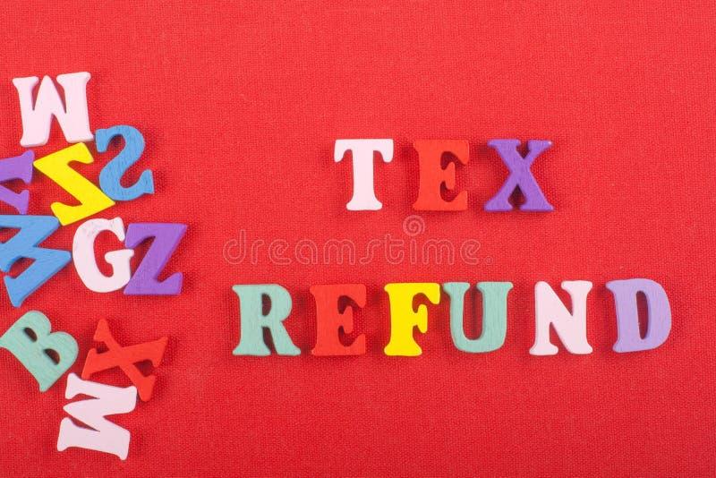 Palavra do REEMBOLSO de TEX no fundo vermelho composto das letras de madeira do bloco colorido do alfabeto do ABC, espaço da cópi fotografia de stock