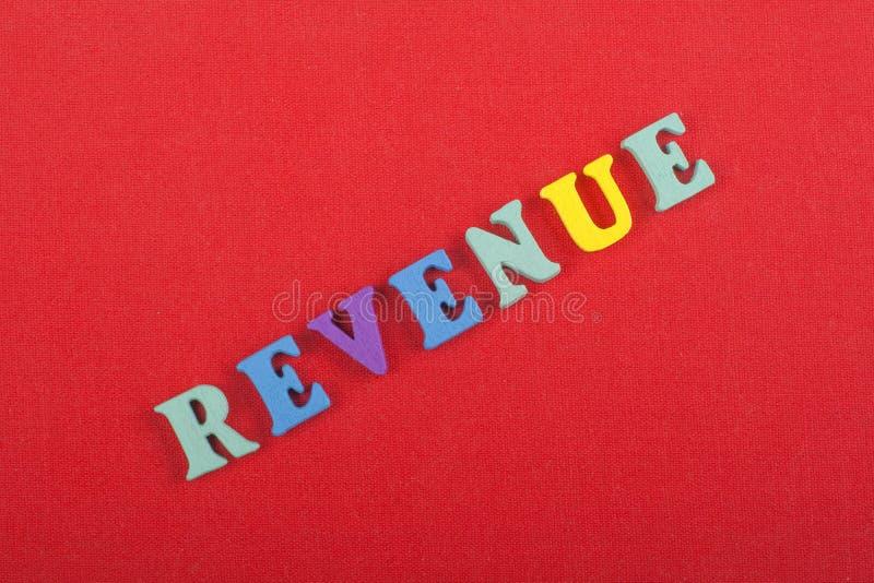 Palavra do RENDIMENTO no fundo vermelho composto das letras de madeira do bloco colorido do alfabeto do ABC, espaço da cópia para foto de stock royalty free