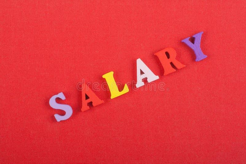 Palavra do SALÁRIO no fundo vermelho composto das letras de madeira do bloco colorido do alfabeto do ABC, espaço da cópia para o  foto de stock royalty free