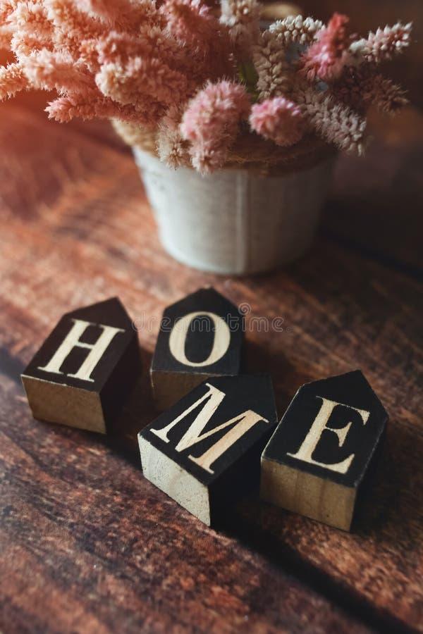 Palavra dos cubos em casa, fundo escuro, flores do verão, tonificadas imagens de stock