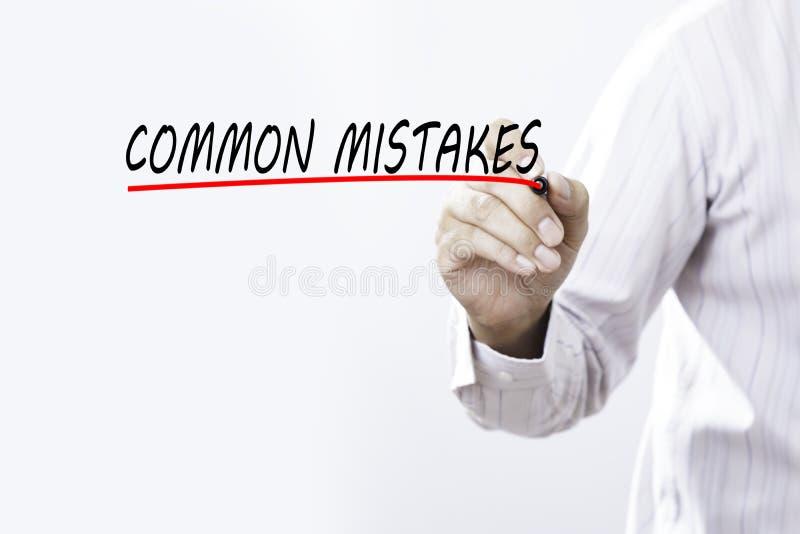 Palavra dos ERROS COMUNS da tração do homem de negócios com o marcador vermelho no transpa imagens de stock