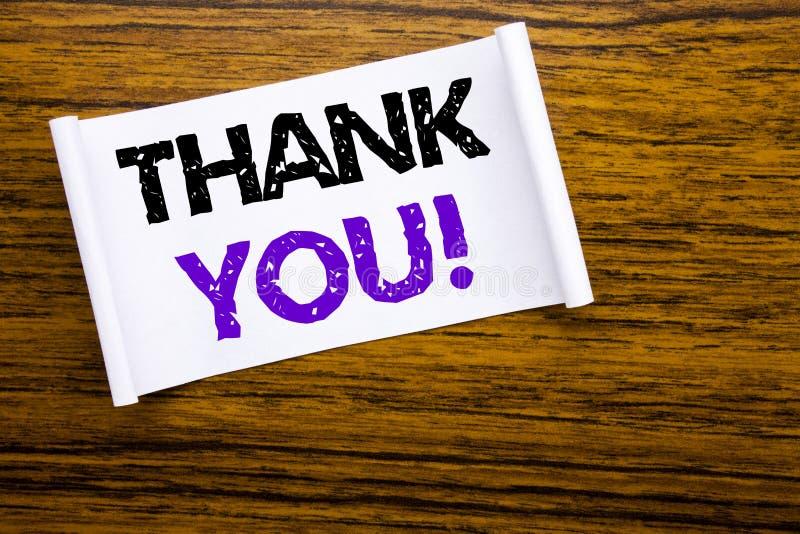 A palavra, escrevendo agradece-lhe Conceito do negócio para a mensagem dos agradecimentos escrita no papel de nota pegajoso no CC foto de stock