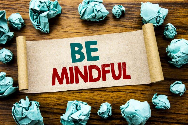 A palavra, escrevendo seja consciente Conceito do negócio para o espírito saudável do Mindfulness escrito no papel de nota pegajo fotos de stock royalty free