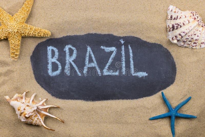 Palavra escrita à mão BRASIL escrito no giz, entre conchas do mar e estrelas do mar imagens de stock