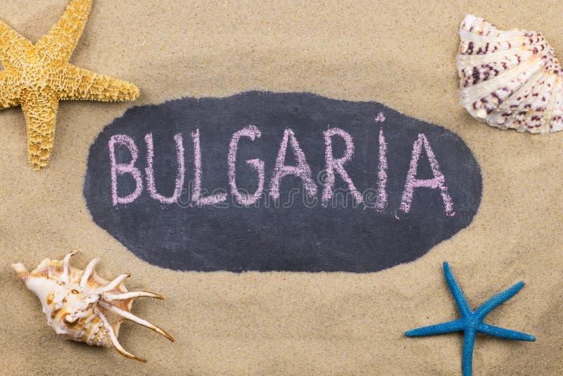 Palavra escrita à mão BULGÁRIA escrita no giz, entre conchas do mar e estrelas do mar imagem de stock