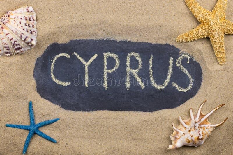Palavra escrita à mão CHIPRE escrito no giz, entre conchas do mar e estrelas do mar fotografia de stock royalty free