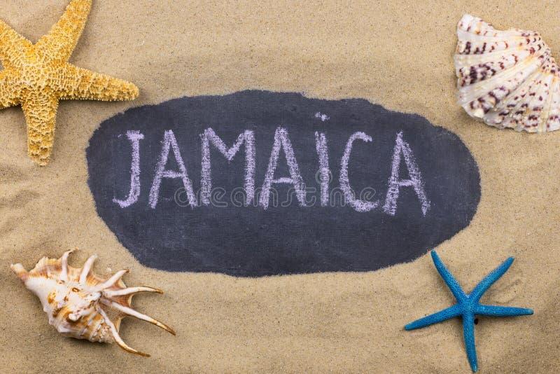 Palavra escrita à mão JAMAICA escrito no giz, entre conchas do mar e estrelas do mar imagens de stock