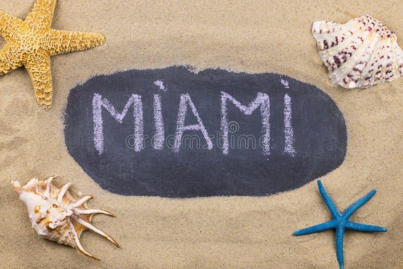 Palavra escrita à mão MIAMI escrito no giz, entre conchas do mar e estrelas do mar fotos de stock royalty free
