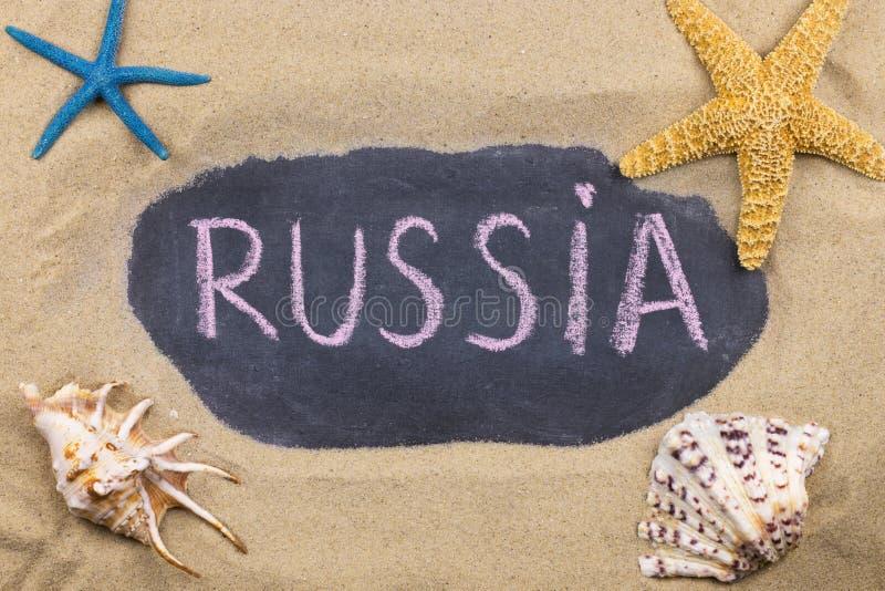 Palavra escrita à mão RÚSSIA escrita no giz, entre conchas do mar e estrelas do mar fotografia de stock royalty free