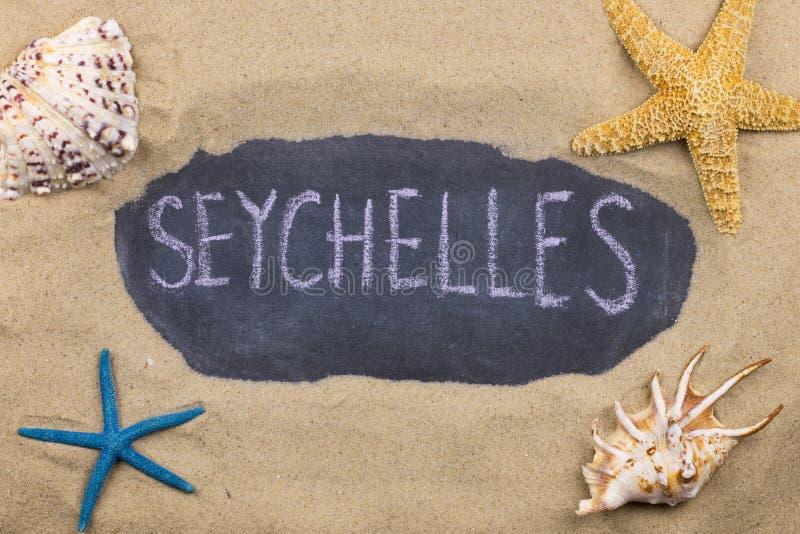 Palavra escrita à mão SEYCHELLES escrito no giz, entre conchas do mar e estrelas do mar foto de stock royalty free