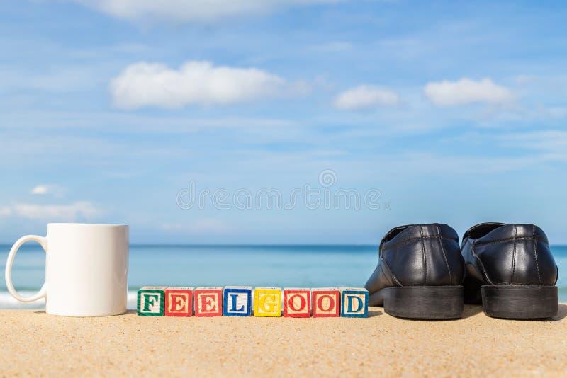 Palavra FEELGOOD em blocos coloridos do alfabeto na praia tropical imagens de stock royalty free