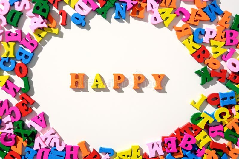 A palavra feliz é alinhada com letras de madeira coloridas em uma tabela branca com dispersado em um círculo com letras foto de stock