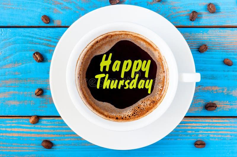 Palavra feliz de quinta-feira no copo de café no fundo de madeira azul borrado com feijões fotografia de stock