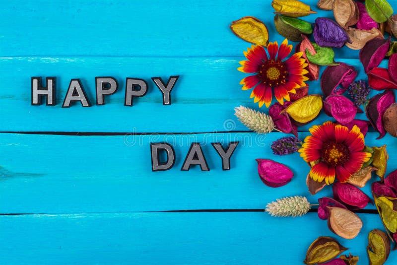 Palavra feliz do dia na madeira azul com flor fotografia de stock royalty free