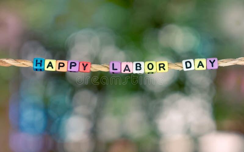 Palavra feliz do Dia do Trabalhador que pendura pela corda com natureza verde bonita fotos de stock royalty free