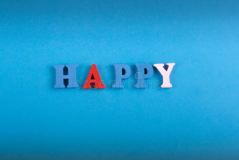 Palavra FELIZ no fundo azul composto das letras de madeira do bloco colorido do alfabeto do ABC, espaço da cópia para o texto do  imagem de stock
