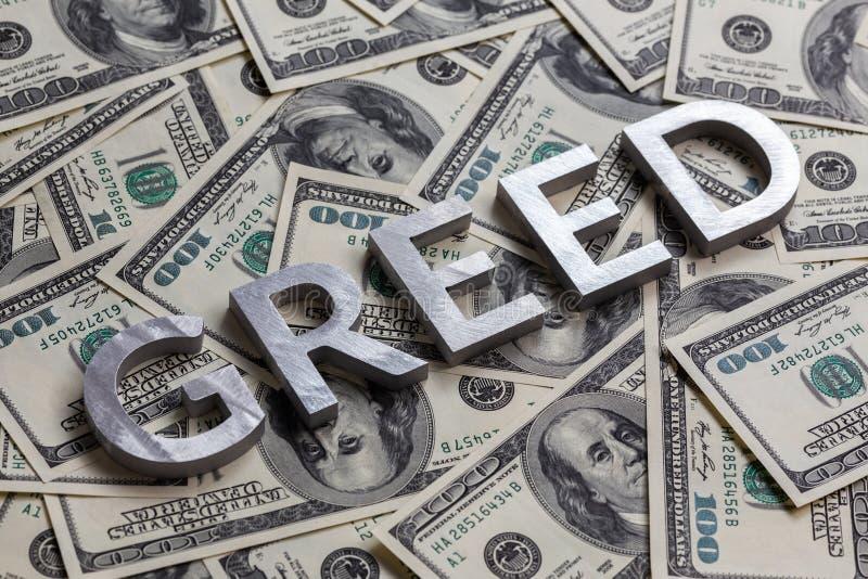 A palavra GREED foi colocada com letras de alumínio sobre o fundo das notas de dólar americano - com foco seletivo imagem de stock royalty free