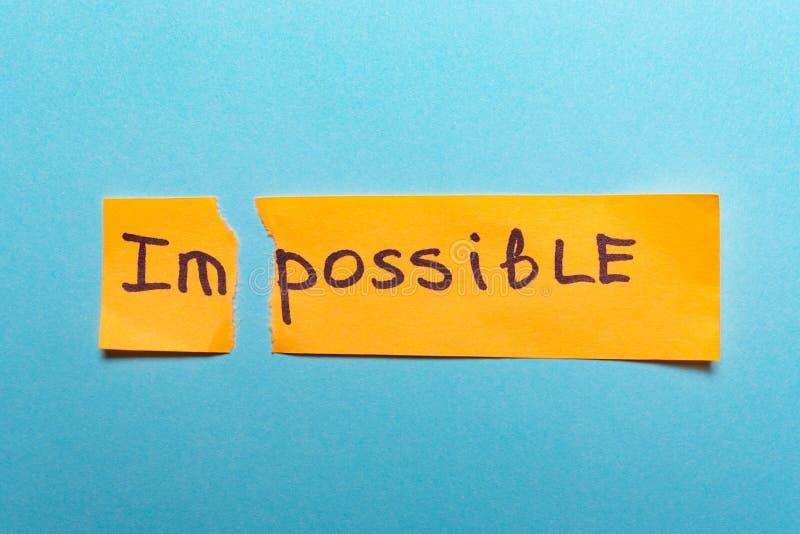 A palavra impossível é escrita no papel amarelo e rasgada em um azul fotos de stock