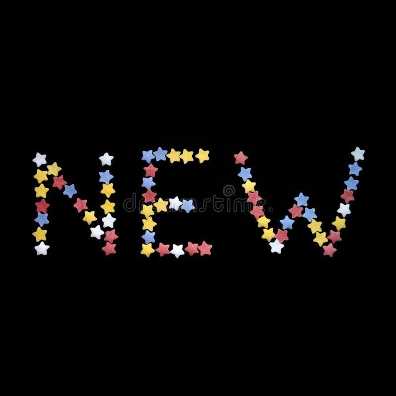 A palavra nova é escrita no tipo grosso de estrelas da pastelaria do açúcar em um fundo preto, para o comércio, vendas no quadrad imagem de stock royalty free