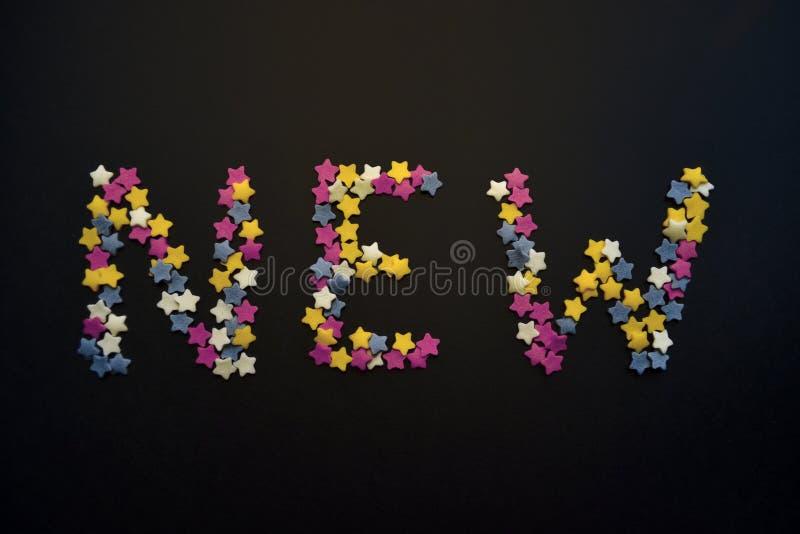 A palavra nova é escrita no tipo grosso de estrelas da pastelaria do açúcar em um fundo preto, para, propaganda, comércio, vendas fotografia de stock