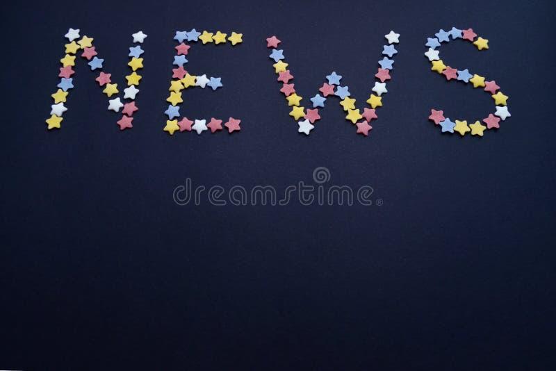 A palavra nova é escrita pelo tipo fino de estrelas da pastelaria do açúcar em um fundo azul, para o comércio, vendas com um copy imagem de stock royalty free