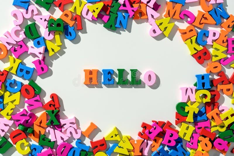 A palavra olá! é letras de madeira coloridas alinhadas em uma tabela branca com dispersado em um círculo com letras imagem de stock