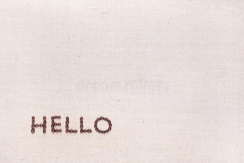 A palavra olá! escrita com os feijões de café disparados de cima de, alinhado no inferior esquerdo fotografia de stock