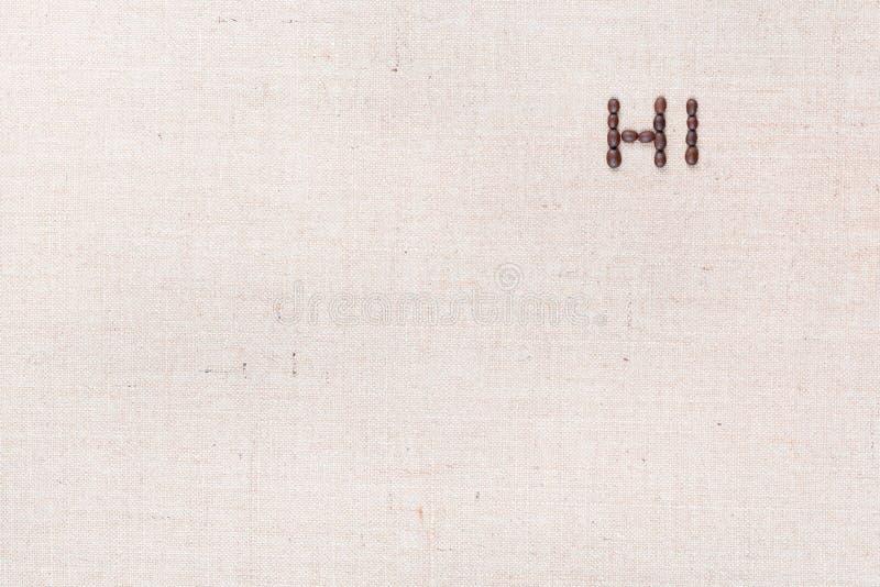 A palavra ol?! escrita com os feij?es de caf? disparados de cima de, alinhado no direito superior fotografia de stock