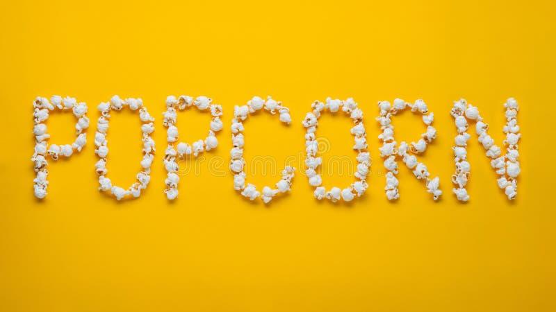 A palavra POPKORN é apresentada das partes de pipoca de sal em um fundo amarelo Vista superior Configuração lisa fotografia de stock