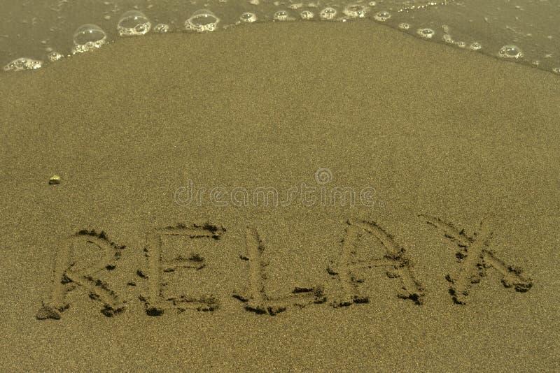 Palavra Relax escrito no Sandy Beach fotografia de stock