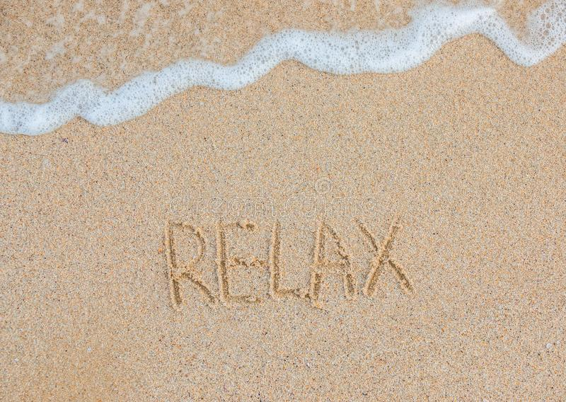 A palavra relaxa escrito à mão no Sandy Beach conceito do curso Férias das horas de verão imagens de stock royalty free