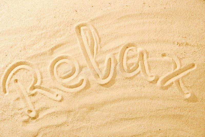 A palavra relaxa na praia da areia imagens de stock royalty free