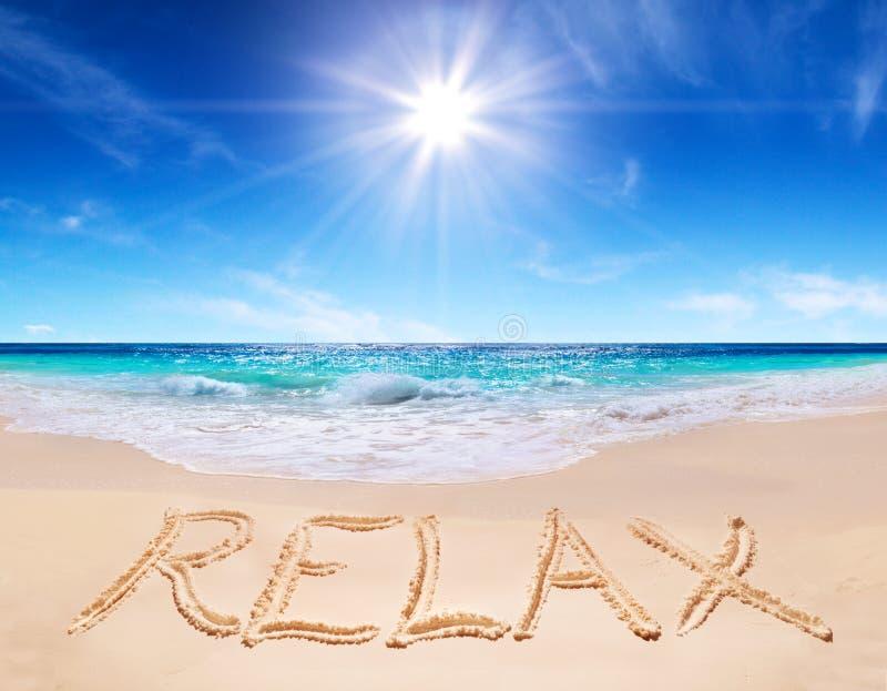 A palavra relaxa na praia tropical imagem de stock royalty free