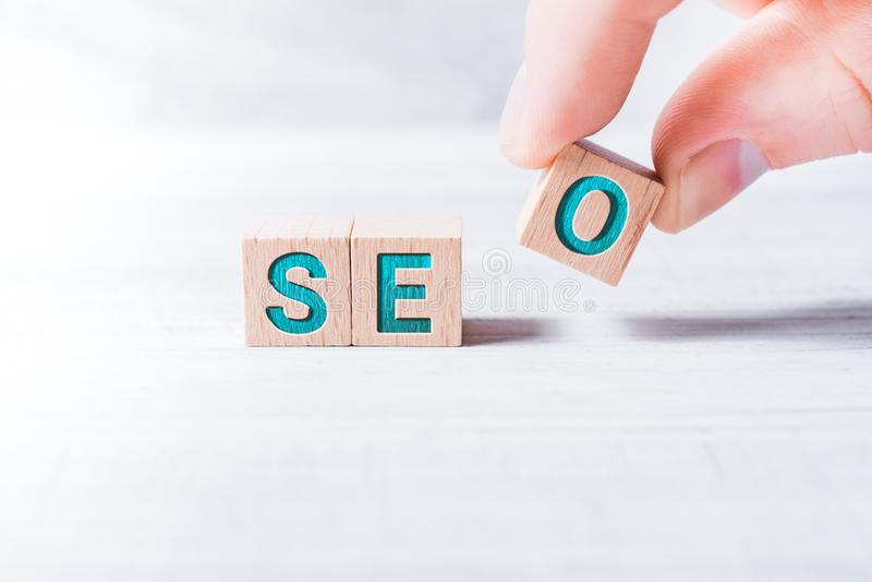 A palavra SEO Formed By Wooden Blocks e arranjado pelos dedos masculinos em uma tabela branca imagem de stock royalty free
