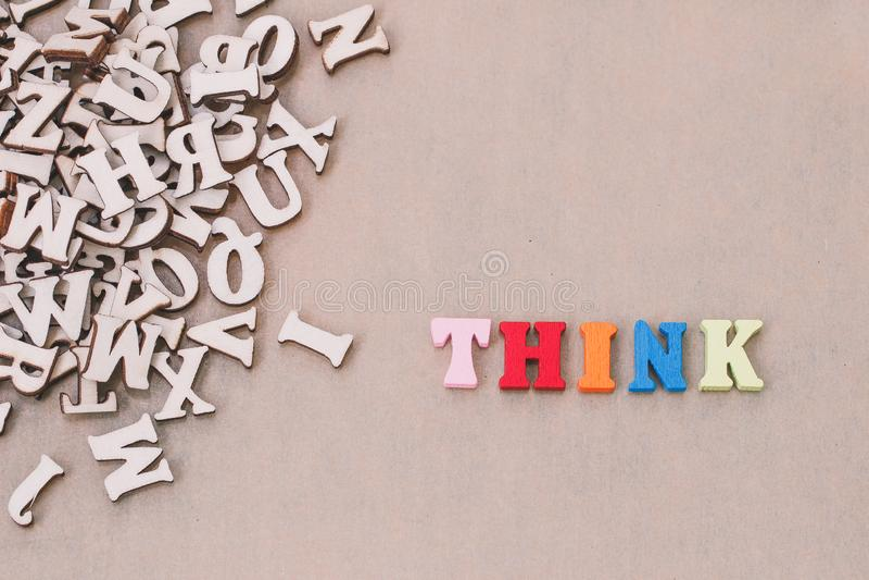 A palavra THINK fez com letras de madeira do bloco ao lado de uma pilha de outras letras imagem de stock royalty free