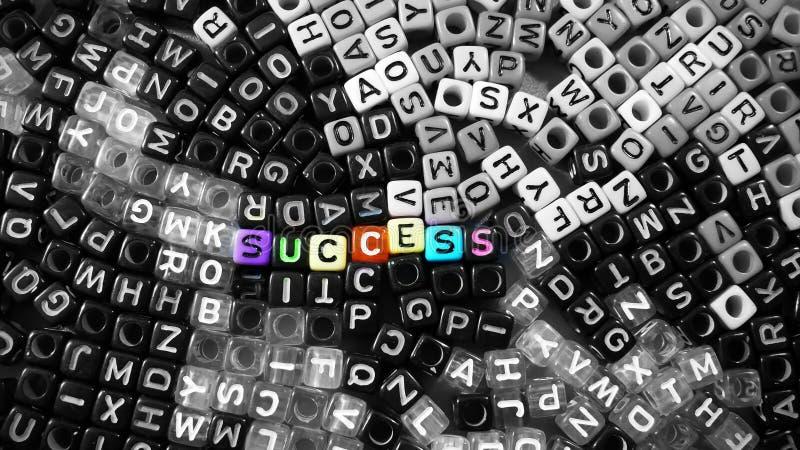 A palavra vívida colorida do sucesso na letra preto e branco do alfabeto cuba o fundo foto de stock
