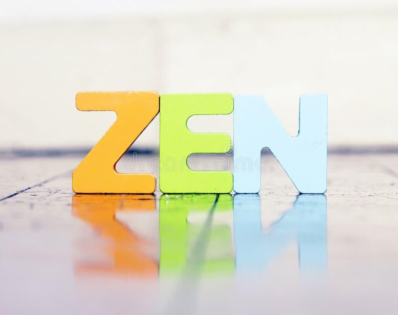 A palavra ZEN com letras de madeira em um assoalho de madeira imagem de stock royalty free