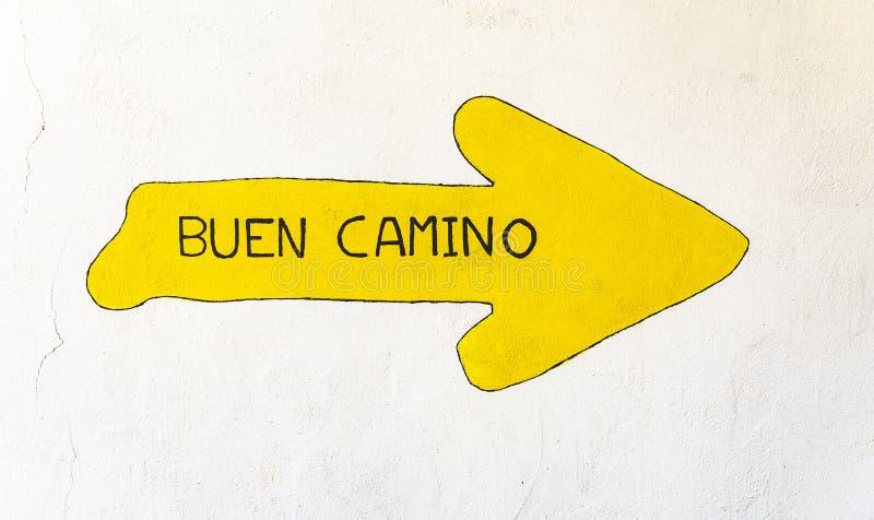 Palavras de Buen Camino em uma seta amarela pintada em uma parede fotografia de stock royalty free