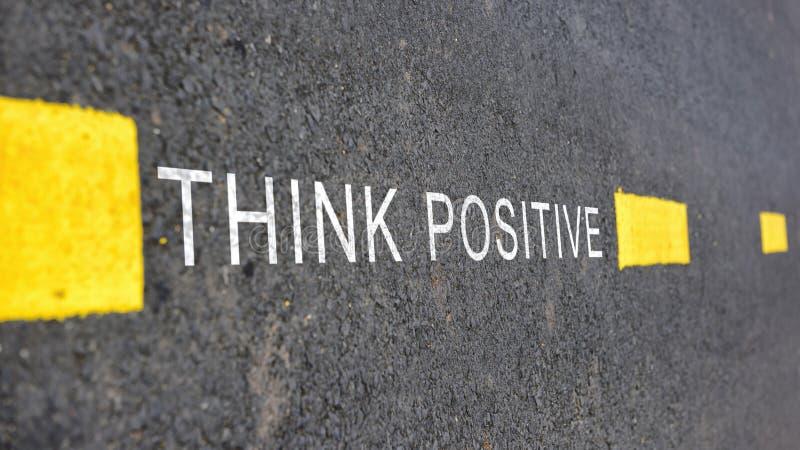 Palavras do positivo Think com linha marcação amarela na superfície de estrada imagens de stock royalty free
