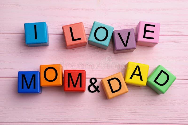 Palavras que eu adoro MÃE e DAD feitas de cubos em mesa de madeira rosa, camada plana fotos de stock
