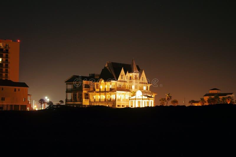 Palazzo acceso della spiaggia contro l'orizzonte di notte fotografia stock libera da diritti