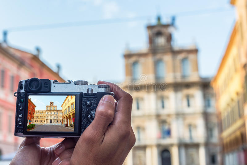 Palazzo Ducale in Piazza Roma of Modena. Italy. Male hands taking a photo of Palazzo Ducale in Piazza Roma of Modena. Emilia-Romagna. Italy royalty free stock image
