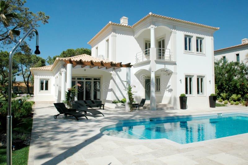 Palazzo moderno di estate con il patio e lo stagno blu immagini stock