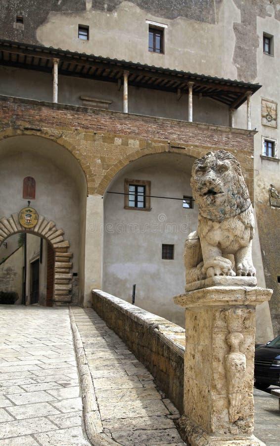 Palazzo Orsini och lejonstaty i den forntida italienska staden Pitiglian arkivbild