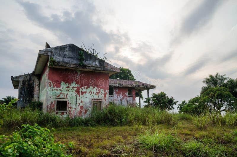 Palazzo rovinato circondato da verde fertile con il cielo drammatico fotografia stock libera da diritti
