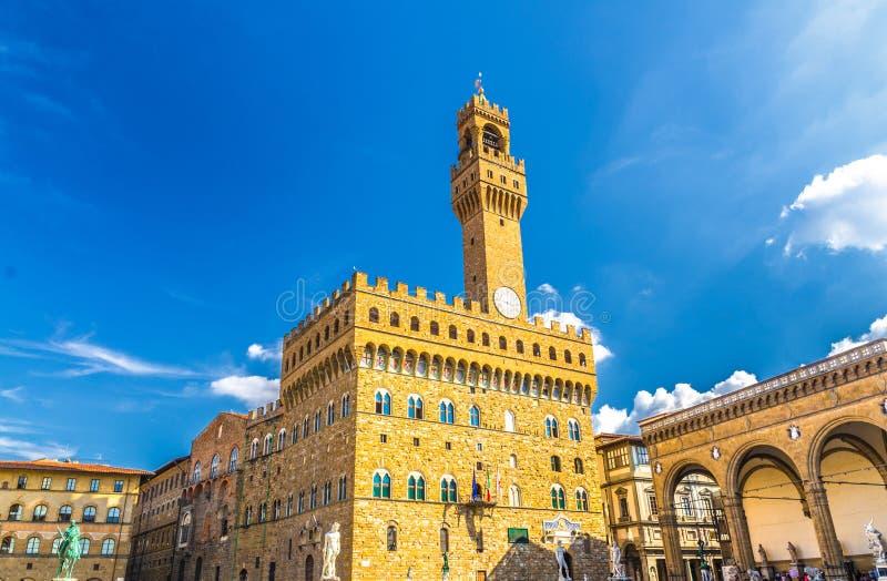 Palazzo Vecchio palace with bell tower with clock and Loggia dei Lanzi on Piazza della Signoria square in historical centre of Flo. Rence city, blue sky white stock photo