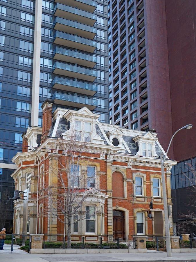 Palazzo vittoriano accoccolato fra le costruzioni di appartamento moderne a Toronto del centro immagine stock