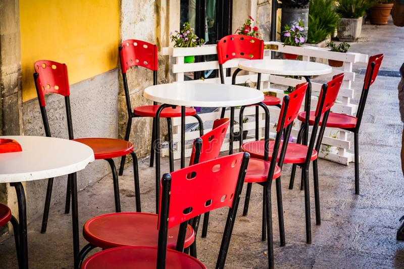 Palazzolo Acreide outdoor restaurant waiting customers. With bright red chairs royalty free stock photos